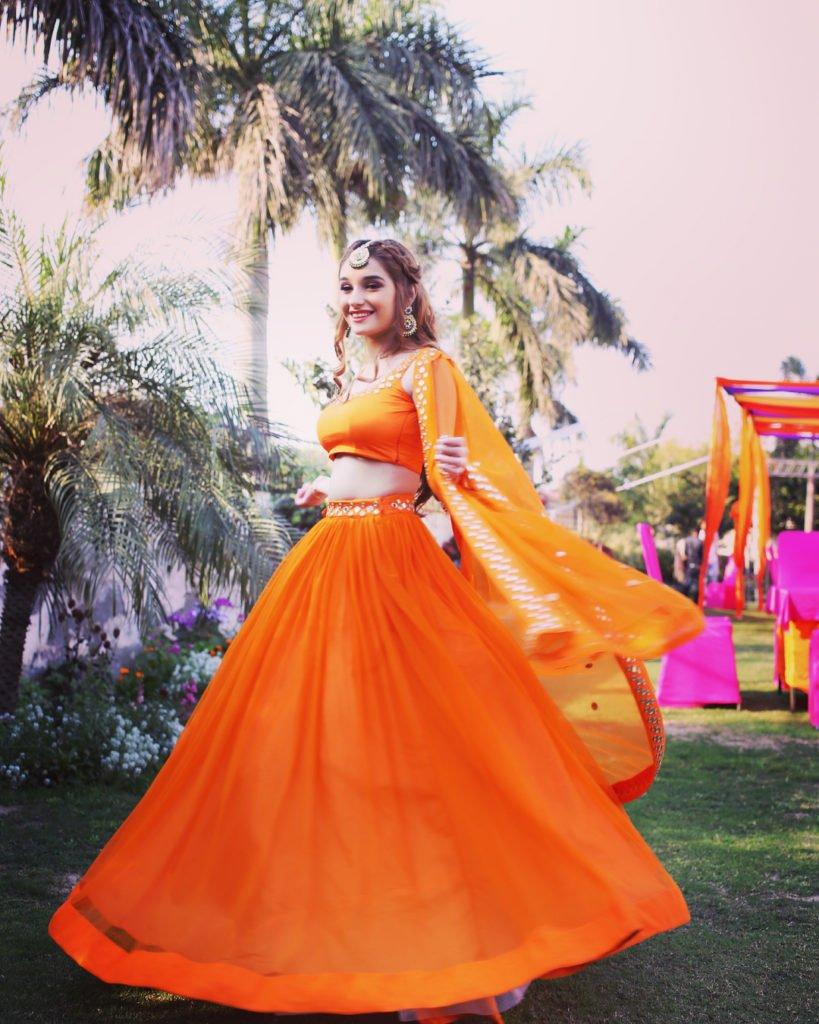 twirling in orange lehenga